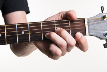 The guitarist's hand clamps the chord Dmon the guitar, on a white background. Horizontal frame