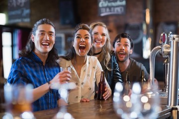 Cheerful friends standing by bar counter