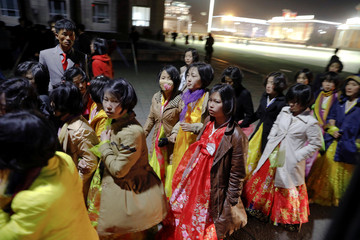 Women dressed in traditional costumes walk near the main Kim Il Sung square in central Pyongyang