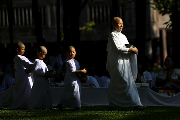 A Buddhist nun walks in line with novice nuns to receive food from people during the Songkran Festival at the Sathira-Dhammasathan Buddhist meditation centre in Bangkok