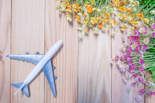 Miniature airplane with artificial flowers on wooden table.