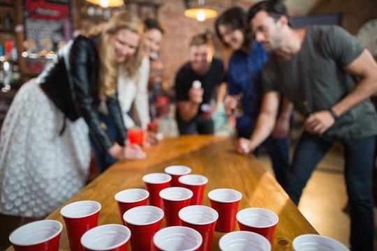 Friends enjoying beer pong game in bar