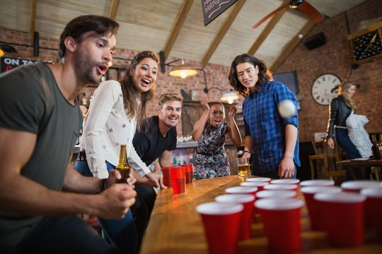 Young friends enjoying beer pong game in restaurant