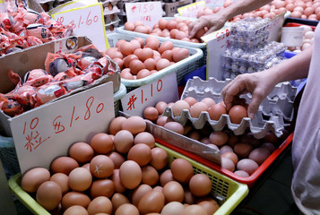 A woman buys eggs at a wet market in Singapore