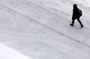 A man walks through the wind and snow in the Brooklyn borough of New York