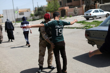 A member of the Iraqi security forces frisks a Muslim man before he enters a mosque for Friday prayers in eastern Mosul