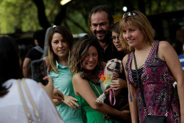 """A family pose for a photo with their dog during a depicted of the Hindu Tihar celebration, a five-day long hindu festival, in whose second day named """"Kukur Puja"""" the dogs or messengers of Lord Yamaraj, the god of death, are worshipped, in Monterrey"""