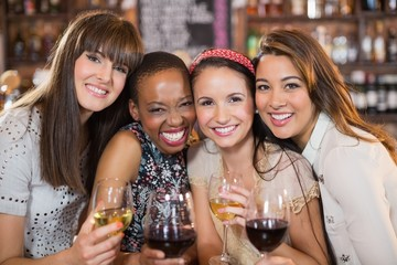 Portrait of happy female friends with wineglasses