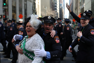 Firefighters pose for a picture with a paradegoer during the St. Patrick's Day Parade in New York City