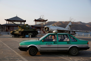A taxi is parked in front of retired airplane and tank on display, at a Chinese village bordering North Korea at Dandong