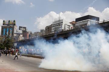 Demonstrators stay away from tear gas fired by security forces during an opposition rally in Caracas