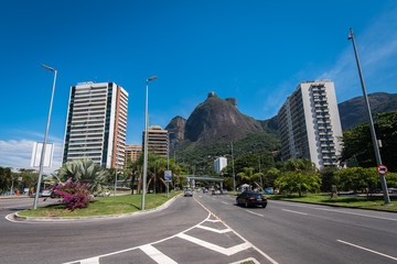 Main avenue crossing Sao Conrado has apartment buildings built along it, and is surrounded by mountains