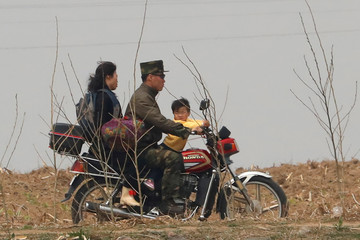 A North Korean soldier rides a motorcycle along the Yalu River in Sinuiju, North Korea, which borders Dandong