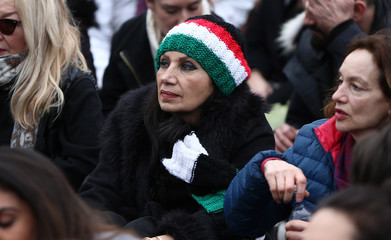 A woman wearing a hat designed in the Iranian national flag colours watches director Asghar Farhadi's film The Salesman on a screen in Trafalgar Square in London
