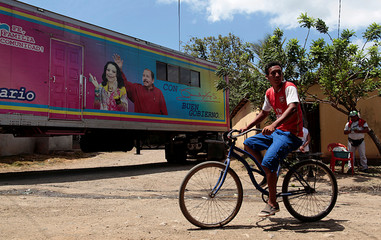 A man ride his bicycle past a picture of Nicaragua's President Daniel Ortega and Vice-President Rosario Murillo placed on a mobile clinic near Popoyuapa National Sanctuary