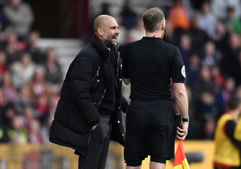 Manchester City manager Pep Guardiola talks to the assistant referee