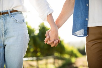 Mid section of couple holding hands