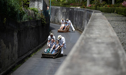 Runners push basket sledges as they descend towards Funchal