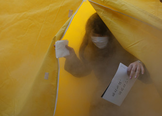 A woman attends an experience in a smoke tent during a disaster drill, one day before the sixth anniversary of the March 11, 2011 earthquake and tsunami that killed thousands and set off a nuclear crisis, in Tokyo
