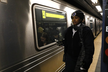 A conductor stands next to a stopped C subway train after a power failure stopped multiple subway lines during the morning commute in New York City