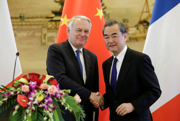 China's Foreign Minister Wang Yi shakes hands with French Foreign Minister Jean-Marc Ayrault in Beijing