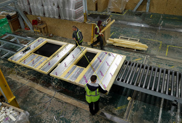 Workers construct timber frame wall sections for a modular Space4 home produced by Persimmon in Birmingham