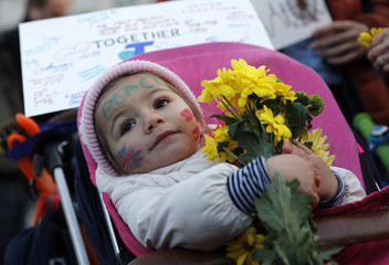 A baby holds a bunch of flowers at a vigil in Trafalgar Square the day after an attack in London