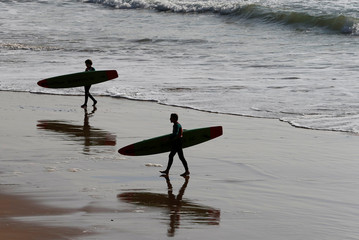 Surfers leave the water after a surf session during an unusually warm spring day on Biarritz beach, southwestern France