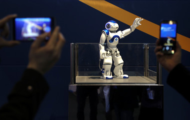 Visitors take pictures of a robot inside NEC's booth during Mobile World Congress in Barcelona