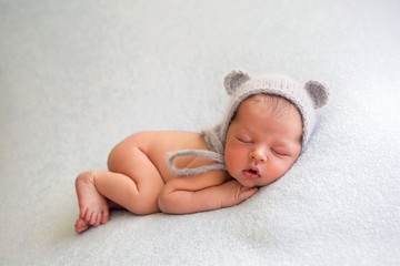 A newborn boy in a naked hat is lying on a light blanket