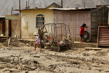 Children play outside their home after rivers breached their banks due to torrential rains, causing flooding and widespread destruction in Huachipa, Lima