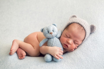 Newborn boy in a naked hat lies on a light blanket with a blue knitted bear