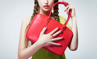 Young woman holding red leather handbag purse. With red manicured nails, lipstick and a ring.