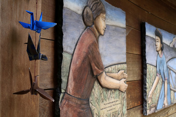 Origami cranes hang near a frieze depicting a separated family at the Japanese American Exclusion Memorial on Bainbridge Island