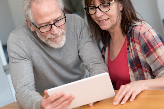 Modern mature couple using tablet