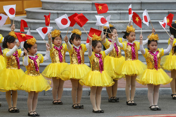 Vietnamese girls waves flags during a welcome ceremony for Japan's Emperor Akihito at the Presidential Palace in Hanoi, Vietnam