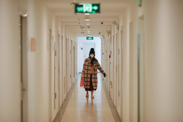 A girl carries a small dog in her bag as she walks inside a dormitory housing broadcasts of live streaming talent agency Three Minute TV, in Beijing
