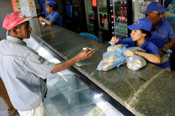 A man buys bread at a bakery in Caracas