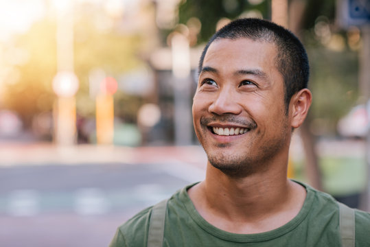 Handsome young Asian man standing on a city street smiling
