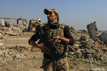 An Iraqi security forces member is pictured beside a destroyed Mosul's airport building after driving out Islamic State's militants south west Mosul