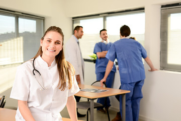 portrait of a young female doctor residential student in hospital office with medical team in background
