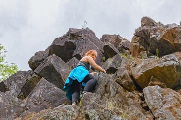 Girl Climbing up Rocks Looking Down