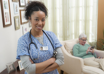 Nurse smiling in home caring for older woman