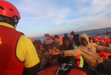 Migrants on an overcrowded plastic raft reach out for life jackets during a search and rescue operation by Spanish NGO Proactiva Open Arms, in central Mediterranean Sea