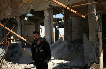 A displaced Iraqi looks out of a destroyed building as Iraqi forces battle with Islamic State militants, in western Mosul