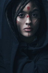 Portrait of beautiful woman with face paint wearing black jacket