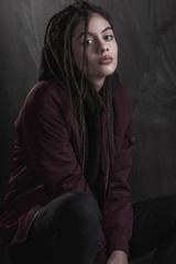 Portrait of a young woman in maroon jacket against black background