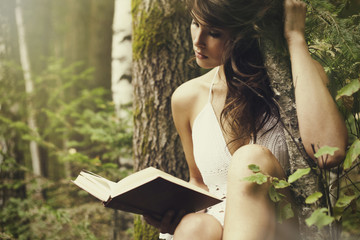 Caucasian woman leaning on tree trunk reading book