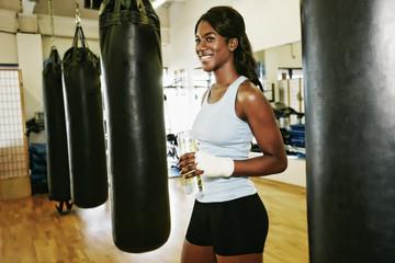 Black woman drinking water near heavy bag in gymnasium