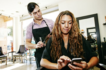 Hairdresser with customer texting on cell phone in hair salon